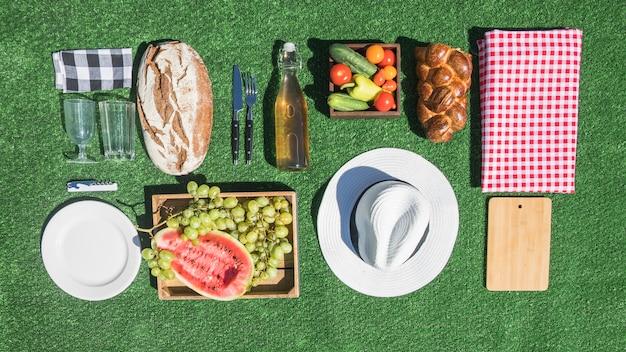 Comida de piquenique; pão; frutas; placa; tábua de cortar; toalha de mesa no relvado verde
