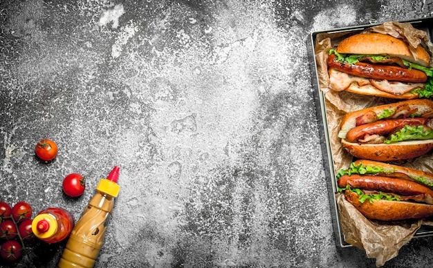 Comida de rua. churrasco de carne de cachorro-quente com molhos picantes na mesa rústica.