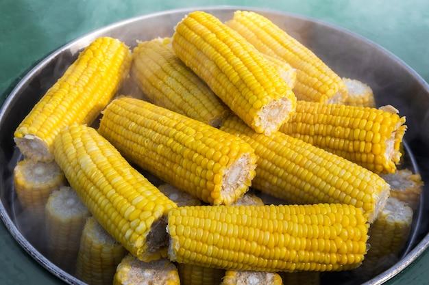 Comida de rua. espigas de milho maduras são cozidas no vapor em uma grande panela de metal.