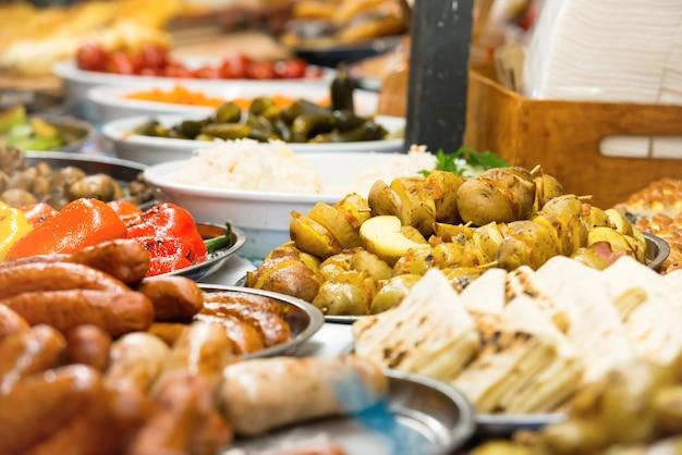 Comida de rua festiva da cozinha tradicional asiática com legumes, carnes e salsichas no mercado