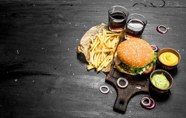 Comida de rua hambúrguer fresco com coca-cola, batatas fritas e molhos no quadro negro