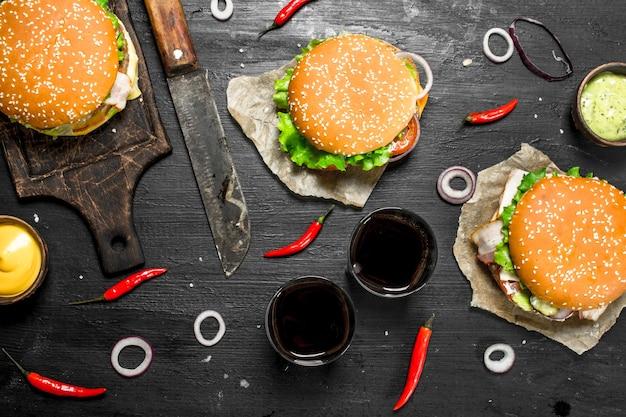 Comida de rua hambúrgueres frescos com carne e vegetais no quadro negro