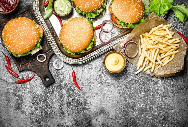 Comida de rua. hambúrgueres frescos com legumes e batatas fritas. sobre um fundo rústico.