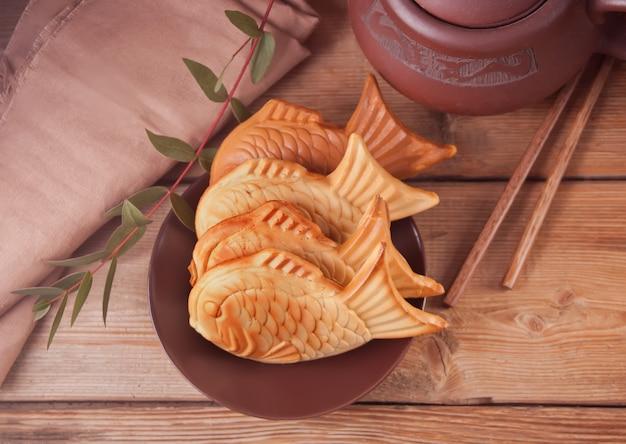 Comida de rua japonesa taiyaki em forma de peixe doce waffle de enchimento na mesa de madeira