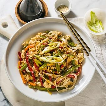 Comida de rua na tailândia - pad thai com tofu em um prato sobre a mesa, em um restaurante ou café
