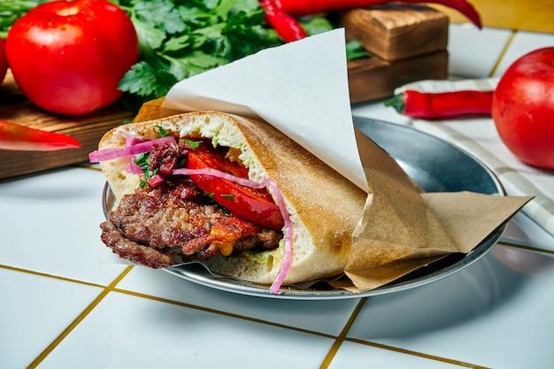 Comida de rua saborosa - pão árabe com tomate, cebola e molho, hambúrguer de carne sobre uma mesa branca. cozinha grega. visão.