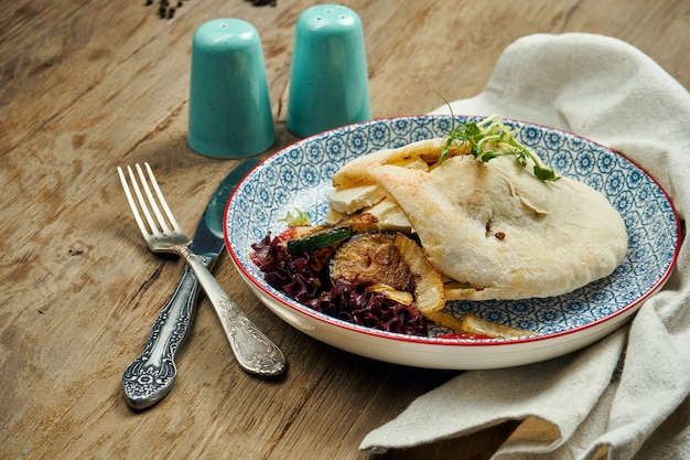 Comida de rua saborosa - pão árabe com tomate, pepino em blate azul na superfície de madeira. cozinha grega. feche acima da vista. shwarma
