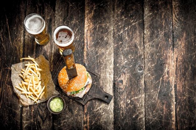 Comida de rua um grande hambúrguer com cerveja em um fundo de madeira