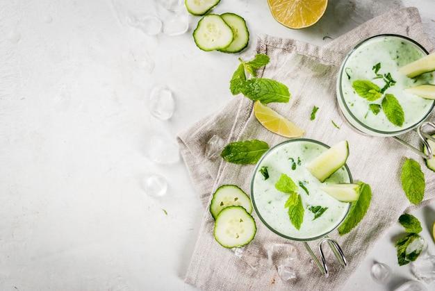 Comida de verão pratos refrescantes sopa fria de pepino abacate com ervas e hortelã com taças com fatias de pepino em uma mesa de concreto branca com ingredientes