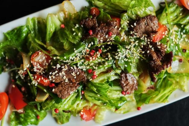 Comida deliciosa: carne cozida lenta puxada com close-up de salada de vegetais frescos em um prato.