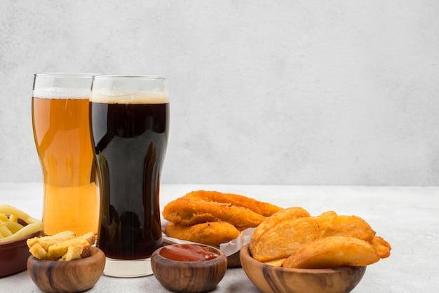 Comida deliciosa e arranjo de copos de cerveja