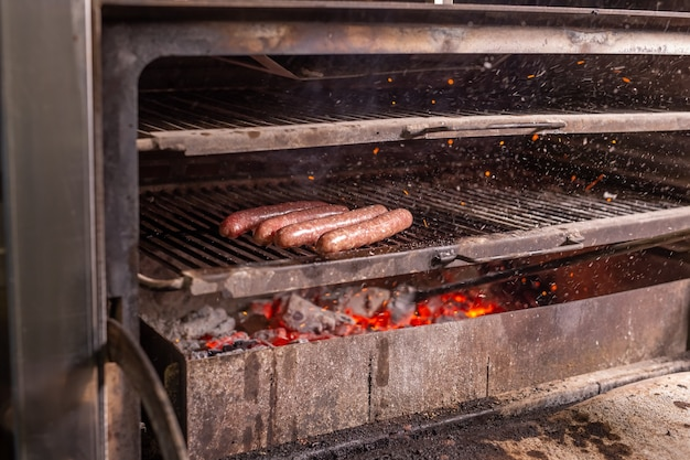 Comida deliciosa e conceito artesanal - linguiça grelhada na grelha em chamas.