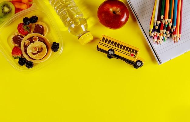 Comida deliciosa em recipiente e lápis coloridos na superfície amarela