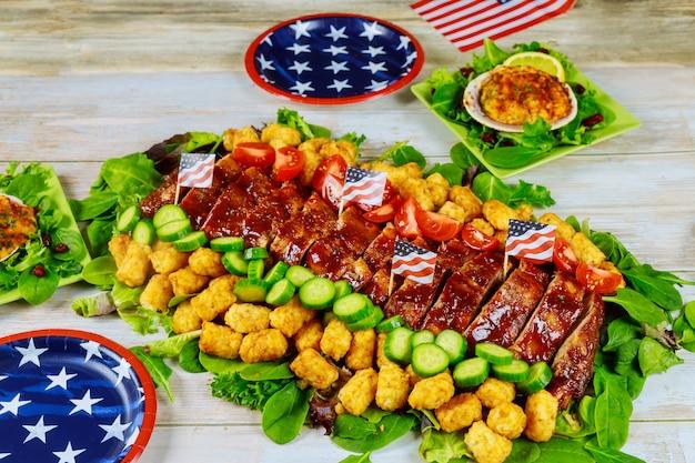Comida deliciosa na mesa de festa com placas padrão americano.
