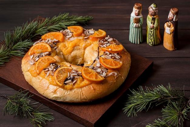 Comida do dia da epifania com laranjas fatiadas e personagens sagrados em miniatura