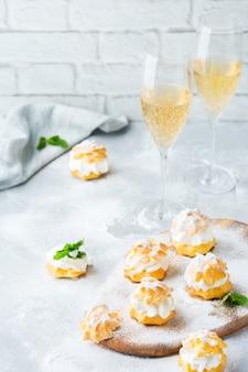 Comida e bebida, conceito de férias. deliciosos profiteroles doces caseiros com creme e copos de champaigne em uma mesa de cozinha moderna