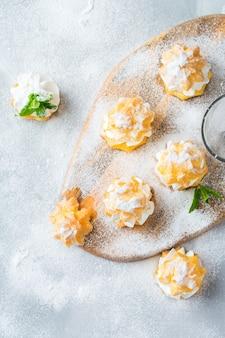 Comida e bebida, conceito de férias. deliciosos profiteroles doces caseiros com creme em uma mesa de cozinha moderna