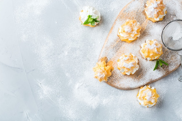Comida e bebida, conceito de férias. deliciosos profiteroles doces caseiros com creme sobre uma mesa de cozinha moderna. copie o fundo do espaço