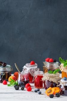 Comida e bebida, conceito de outono de verão de colheita. variedade de frutas da estação e compotas de frutas em potes sobre uma mesa de madeira. copie o fundo rústico do espaço