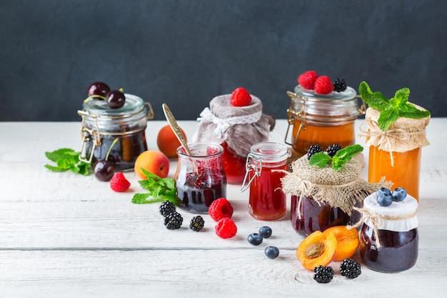 Comida e bebida, conceito de outono de verão de colheita. variedade de frutas da estação e compotas de frutas em potes sobre uma mesa de madeira. fundo rústico