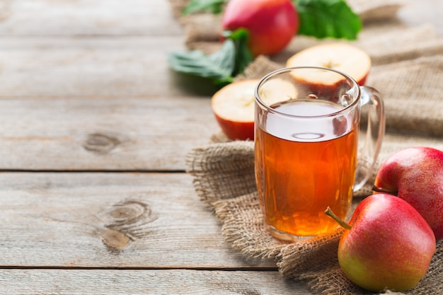 Comida e bebida, conceito de outono outono da colheita. suco de maçã orgânico fresco em uma caneca com frutas maduras em fundo de madeira rústico. copie o espaço