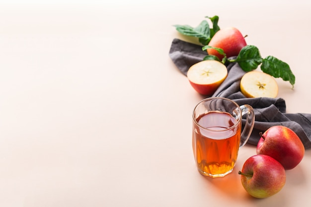 Comida e bebida, conceito de outono outono da colheita. suco de maçã orgânico fresco em uma caneca com frutas maduras no fundo coral rosa da moda. copie o espaço
