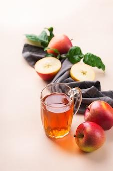 Comida e bebida, conceito de outono outono da colheita. suco de maçã orgânico fresco em uma caneca com frutas maduras no fundo coral rosa da moda