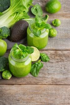Comida e bebida, dieta e nutrição saudáveis, estilo de vida, conceito vegano, alcalino, vegetariano. smoothie verde com ingredientes orgânicos, vegetais em uma mesa de cozinha de madeira. copie o fundo do espaço