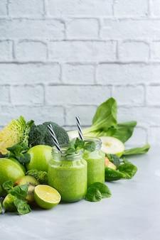 Comida e bebida, dieta e nutrição saudáveis, estilo de vida, conceito vegano, alcalino, vegetariano. smoothie verde com ingredientes orgânicos, vegetais em uma mesa de cozinha moderna. copie o fundo do espaço