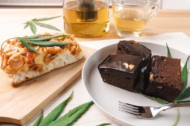 Comida e bebida e folhas de cannabis na mesa de jantar. conceito de medicina alternativa.