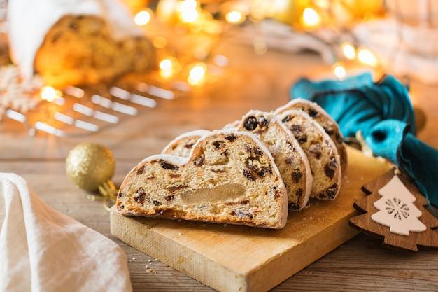 Comida e bebida sazonal, conceito de inverno. bolo de natal caseiro alemão tradicional europeu, sobremesa pastelaria stollen em fundos de madeira com decoração festiva.