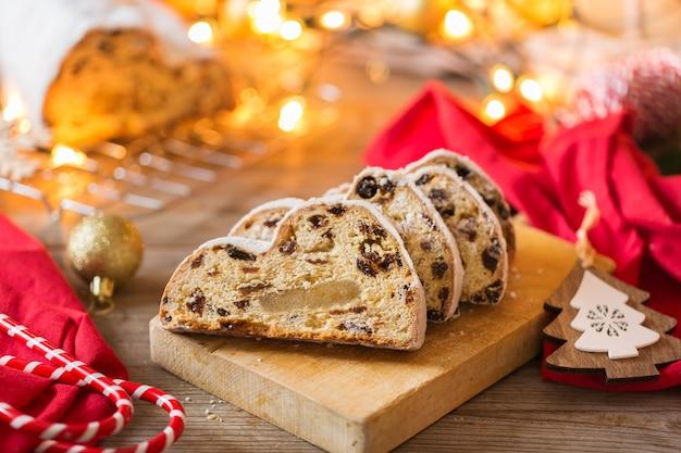 Comida e bebida sazonal, conceito de inverno. bolo de natal caseiro alemão tradicional europeu, sobremesa pastelaria stollen em um fundos de madeira com decoração festiva.