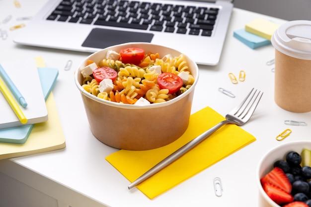 Comida em tirar caixas na mesa branca com laptop.