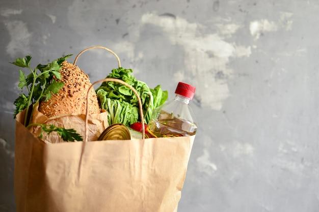 Comida em um saco de papel. doação de alimentos ou conceito de entrega de alimentos. óleo, pão, repolho, salada, legumes, comida enlatada.