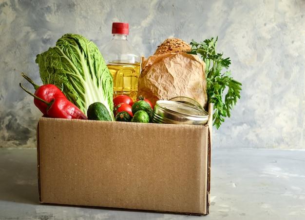 Comida em uma caixa de papelão. doação de alimentos ou conceito de entrega de alimentos. óleo, couve, salada, legumes, comida enlatada.