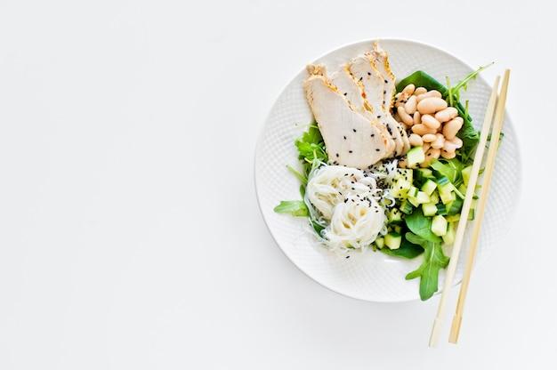Comida equilibrada saudável, tigela de macarrão de vidro, feijão, peito de frango, espinafre, rúcula e pepino