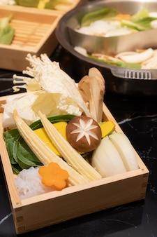 Comida fresca consiste em cogumelos, vegetais e macarrão, servidos em uma caixa quadrada de madeira