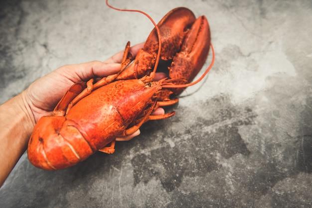 Comida fresca de lagosta vermelha na mão e placa preta