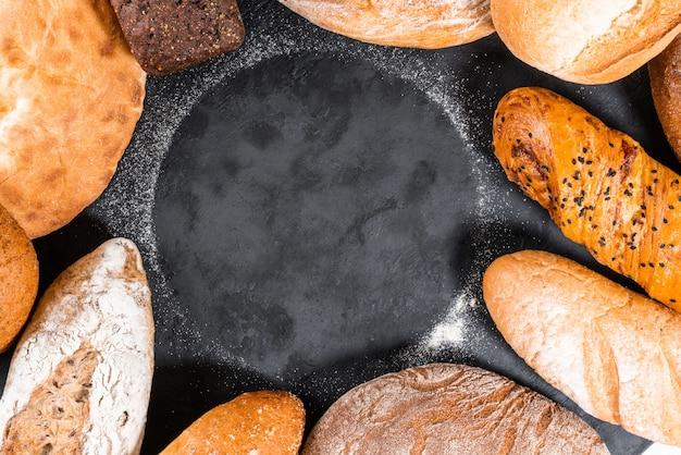 Comida fresca de padaria, nacos de pão duros rústicos em fundo de pedra preto. vista do topo