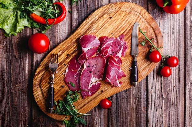 Comida fresca e saudável. carne vermelha fatiada situa-se na mesa de madeira com rúcula