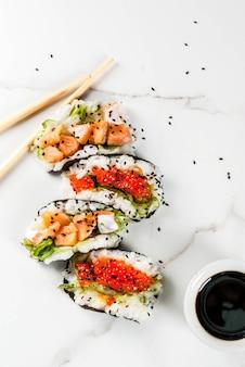 Comida híbrida de tendência. cozinha asiática japonesa. mini sushi-tacos, sanduíches com salmão, hayashi wakame