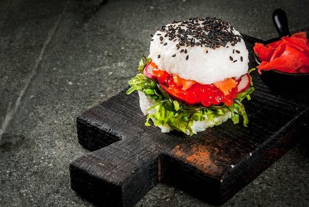 Comida híbrida de tendência. cozinha asiática japonesa. sushi-hambúrguer, sanduíche com salmão, hayashi wakame, daikon, gengibre, caviar vermelho. mesa de pedra preta, com molho de soja. copie o espaço