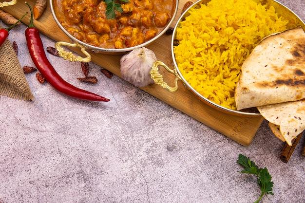 Comida indiana. frango com curry em molho de tomate e arroz amarelo, copie o espaço
