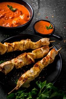 Comida indiana. prato tradicional frango tikka masala picante, caril de frango manteiga, com pão naan indiano manteiga, especiarias, ervas.