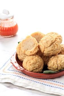 Comida indonésia: bakso goreng, almôndega frita da indonésia. feito de carne de frango ou camarão e farinha, servido em prato marrom com molho chinês picante