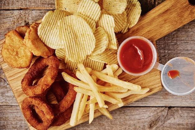 Comida insalubre e lixo. diferentes tipos de fastfood e lanches na mesa, close-up. comida para levar