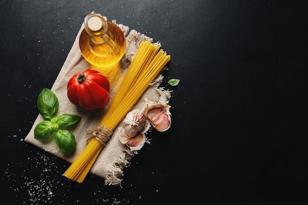 Comida italiana com legumes espaguete e molho de tomate na mesa escura. vista do topo.