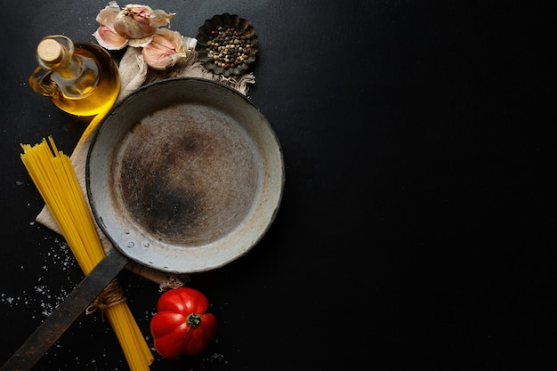 Comida italiana com legumes espaguete e panela na mesa escura. vista do topo.