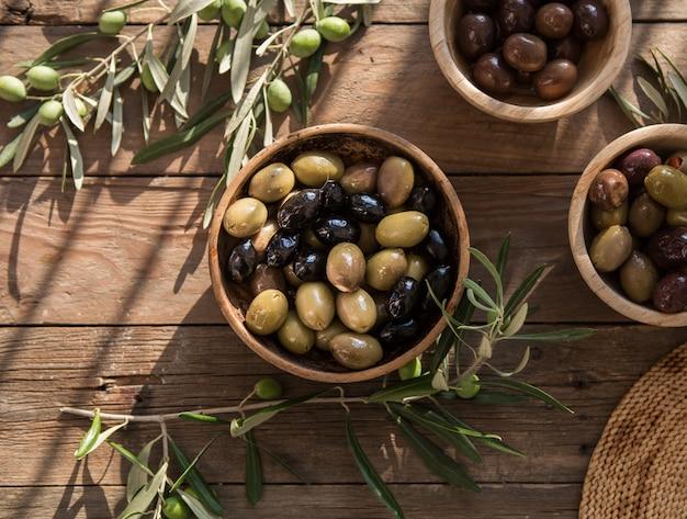 Comida italiana, com pimentão e azeitonas verdes, recheadas com queijo, azeitonas pretas, azeite na mesa de madeira