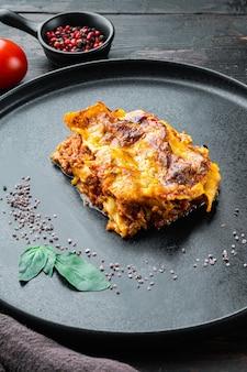 Comida italiana. conjunto de lasanha quente saborosa recém-assada, no prato, na velha mesa de madeira escura